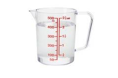 Taza de medición plástica de la cocina llenada de agua Fotografía de archivo