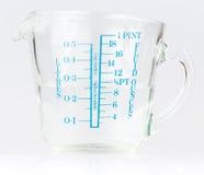 Taza de medición que contiene el agua fotos de archivo