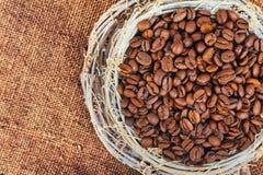 Taza de mimbre con los granos de café en un fondo del yute Imagen de archivo libre de regalías
