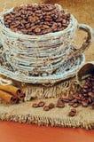 Taza de mimbre con los granos y el canela de café en un fondo del yute Fotografía de archivo