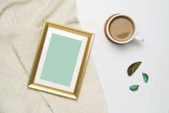 Taza de mofa del marco de la foto del café y del oro para arriba en el hilado marrón y el fondo de madera blanco fotografía de archivo
