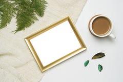 Taza de mofa del marco de la foto del café y del oro para arriba en el hilado marrón y el fondo de madera blanco imagenes de archivo