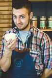 Taza de ofrecimiento del barista joven feliz de café a ir a sonreír en la cámara imagen de archivo