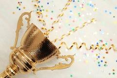 Taza de oro del trofeo con las flámulas en fondo de madera imagen de archivo
