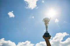 Taza de oro del trofeo contra el cielo foto de archivo