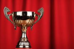Taza de oro del trofeo sobre fondo rojo imagen de archivo libre de regalías