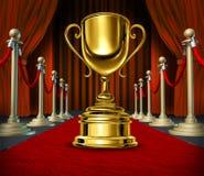 Taza de oro en una alfombra roja con las cortinas del terciopelo Imagen de archivo libre de regalías