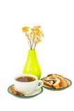 Taza de palillos del té y de un canela del bollo cerca del florero Imagenes de archivo