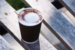 Taza de papel con café en el banco en parque Fotografía de archivo libre de regalías