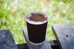 Taza de papel con café en el banco en parque Imagen de archivo libre de regalías
