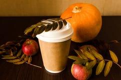 Taza de papel con café en fondo del otoño Fotografía de archivo libre de regalías