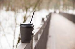 Taza de papel con los soportes del caf? en una barandilla del metal en el puente imagen de archivo