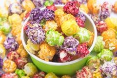 Taza de papel con palomitas del caramelo en el fondo del maíz multicolor imágenes de archivo libres de regalías