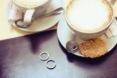 Taza de pares de oro de la boda del caf? para la fecha rom?ntica de los amantes fotografía de archivo libre de regalías