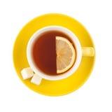Taza de té amarilla con el azúcar y el limón Foto de archivo