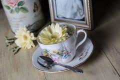 Taza de té antigua con las flores amarillas de la margarita Imágenes de archivo libres de regalías