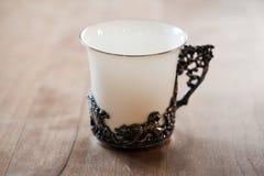 Taza de té antigua de la porcelana en la tabla del cordón Fotos de archivo