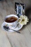 Taza de té antigua por completo del té con la flor amarilla de la margarita y la fotografía vieja Fotos de archivo libres de regalías
