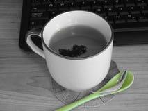 Taza de té bonita por el teclado foto de archivo