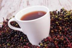 Taza de té caliente con el jugo de la baya del saúco y montón de la baya, nutrición sana Fotos de archivo libres de regalías