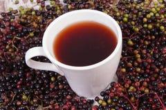 Taza de té caliente con el jugo de la baya del saúco y montón de la baya, nutrición sana Imágenes de archivo libres de regalías