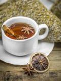 Taza de té caliente con los palillos de canela y el limón secado delicioso Imagen de archivo