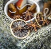 Taza de té caliente con los palillos de canela y el limón secado delicioso Fotografía de archivo