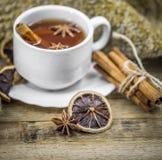 Taza de té caliente con los palillos de canela y el limón secado delicioso Fotos de archivo libres de regalías
