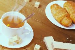 Taza de té caliente con vapor y un cruasán, una oblea y una tostada en una tabla de madera vieja Fotografía de archivo libre de regalías