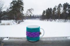 Taza de té caliente en una cubierta de punto Foto de archivo libre de regalías