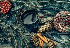 Taza de té caliente en una tabla de madera rústica Todavía la vida de conos, canela, abeto ramifica Preparación para la Navidad Foto de archivo