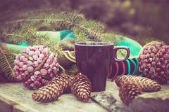 Taza de té caliente en una tabla de madera rústica Todavía la vida de conos, guita, bramante, abeto ramifica Preparación para la  Imagen de archivo