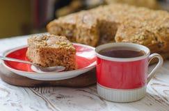 Taza de té caliente y pedazo de torta de miel en el platillo rojo Estilo rústico imagen de archivo libre de regalías