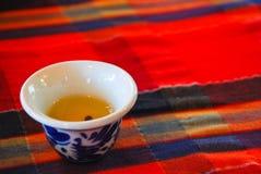 Taza de té china en tela roja Imagenes de archivo