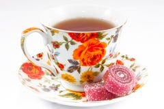 Taza de té clásica con las flores rojas y anaranjadas Fotografía de archivo