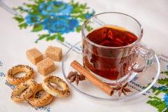Taza de té con el azúcar marrón, el anís, el canela y los panecillos Imagen de archivo