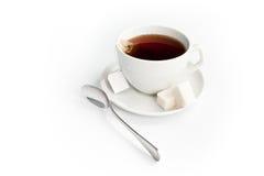 Taza de té con el azúcar y la bolsita de té aislados en blanco Imagenes de archivo
