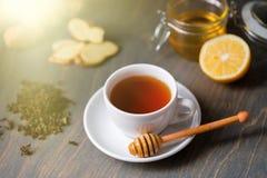 Taza de té con el limón, el jengibre, la miel y el palillo de la miel en la tabla rústica de madera imagen de archivo