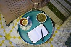 Taza de té con el limón, la infusión de hierbas natural y el cuaderno con la pluma imagenes de archivo