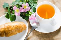 Taza de té con el limón y el cruasán Fotos de archivo