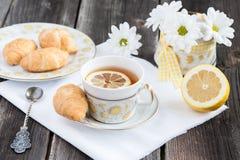 Taza de té con el limón y el cruasán Imagen de archivo libre de regalías