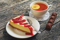 Taza de té con el limón y el pastel de queso en un fondo de madera Foto de archivo libre de regalías