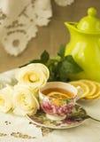 Taza de té con el limón y las rosas blancas en una servilleta bordada Fotografía de archivo libre de regalías