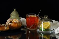 Taza de té con el limón y los rollos dulces Fotografía de archivo libre de regalías