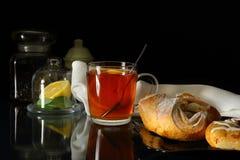 Taza de té con el limón y los rollos dulces Imagenes de archivo