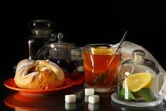Taza de té con el limón y los rollos dulces Imágenes de archivo libres de regalías