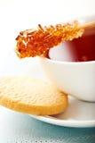 Taza de té con el palillo y la galleta de swizzle del azúcar Imagenes de archivo