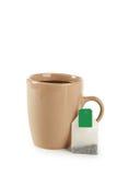 Taza de té con la bolsita de té aislada en blanco Fotos de archivo libres de regalías