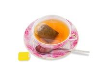 Taza de té con la bolsita de té, cuchara en el platillo Imagen de archivo