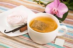 Taza de té con la bolsita de té y la melcocha rosada en un platillo con una vainilla, canela Imagen de archivo